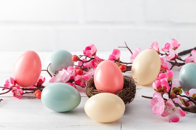 Close up of colorful easter eggs in the nest with pink plum flower on bright white wooden table surface.