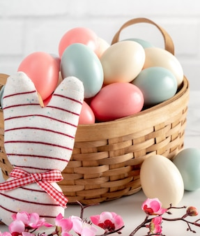 Close up of colorful easter eggs in the nest with pink plum flower on bright white wooden table.