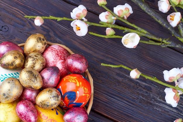 カラフルな卵と春の花のクローズアップ。木製のテーブルの上の雑多なホイルの卵の上面図の山。