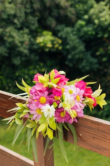 Close-up of colorful flower bouquet tied on wooden railing on wedding ceremony