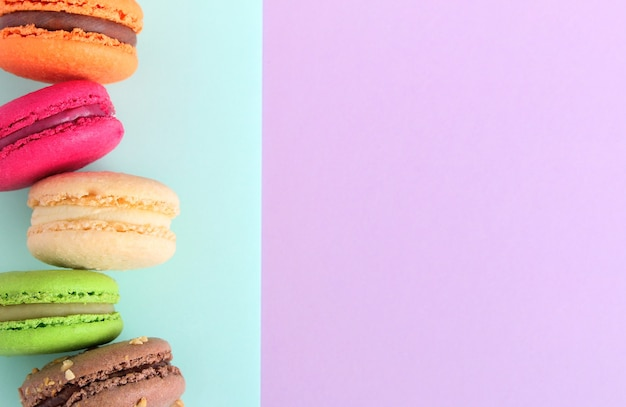 Close up of colorful french macaroons on mint and purple background