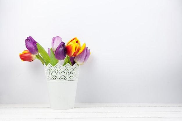 Close-up of colorful fresh tulip flowers in white vase