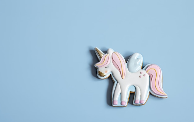 Close-up of colorful gingerbread in the shape of a unicorn on a blue background, copy space.