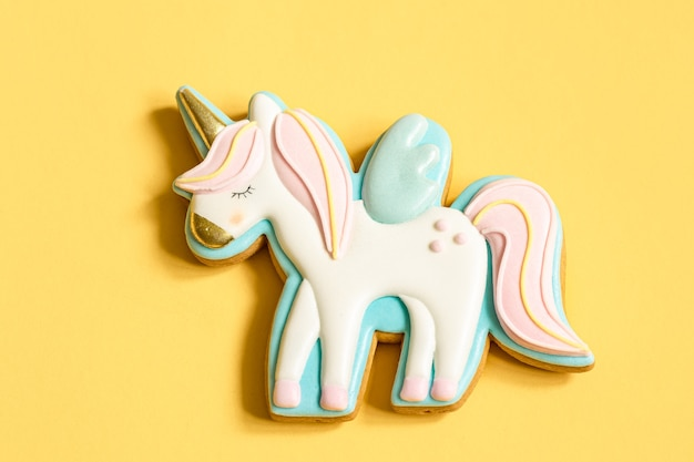 Close-up of colorful gingerbread in the shape of a unicorn on a yellow background.