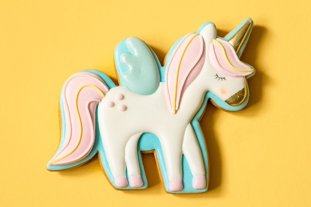 Close-up of colorful gingerbread in the shape of a unicorn on a yellow surface.