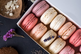 Close up colorful macarons dessert with vintage pastel tones on wooden background