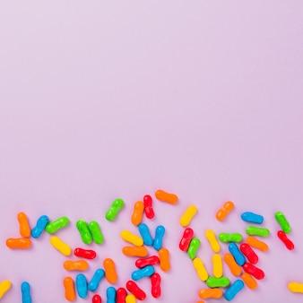 Close-up di caramelle di marmellata colorata su sfondo rosa