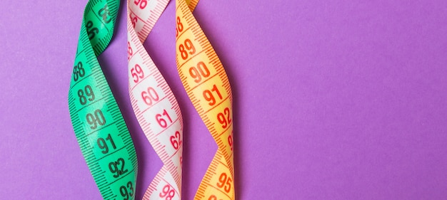Close up of colorful measure tapes on purple background. perfect female figure measurements concept.