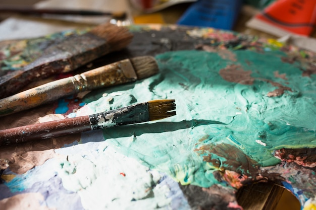 Close-up of colorful messy old paint brush and palette