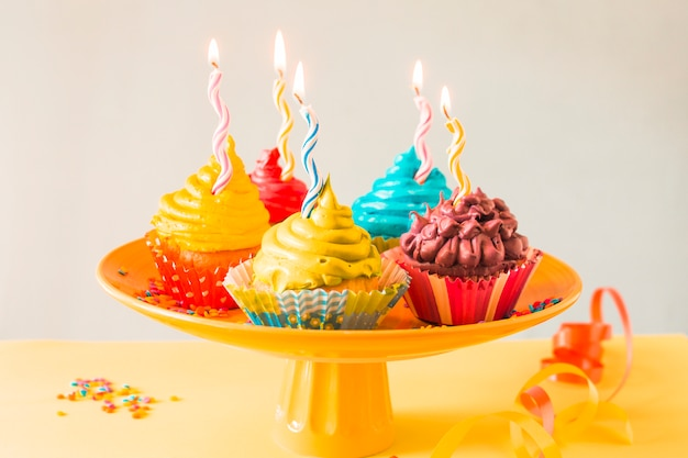 Close-up of colorful muffins with illuminated candles on cakestand