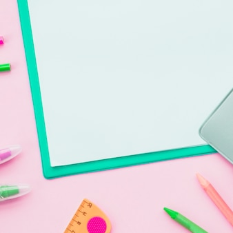Close-up of colorful pencil and white paper on pink surface