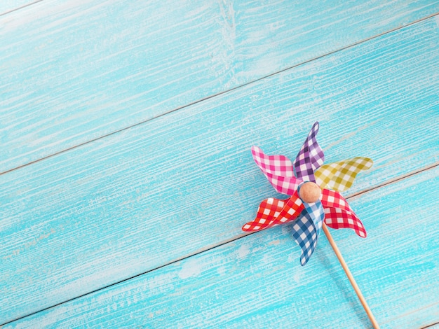 Close up colorful pinwheel over blue wooden surface