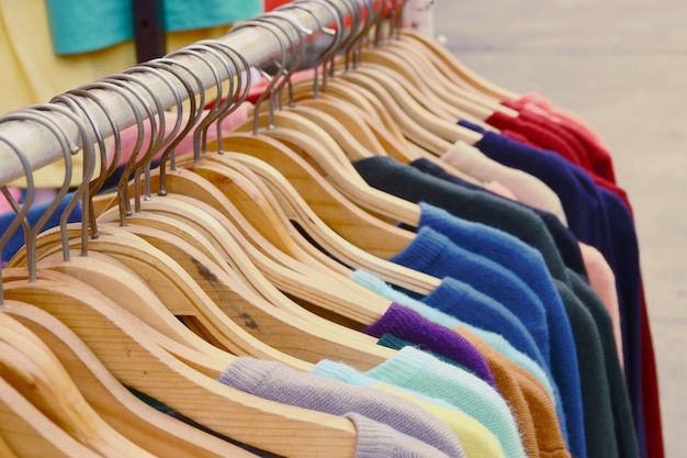 Close up colorful t shirts are hanging on rack