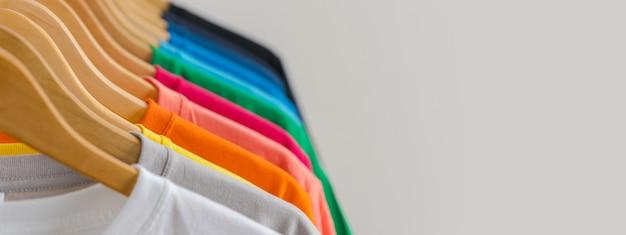 关闭在挂衣架的五颜六色的T恤杉,服装背景
