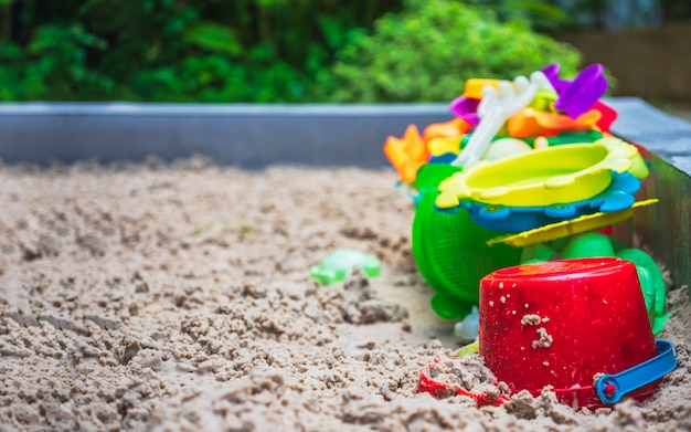 Close up of colorful toys on sand playground.