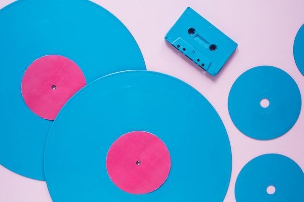 Крупноформатная компактная кассета возле пластиковых дисков