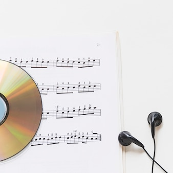 Close-up of compact disc on musical note with earphone on white background
