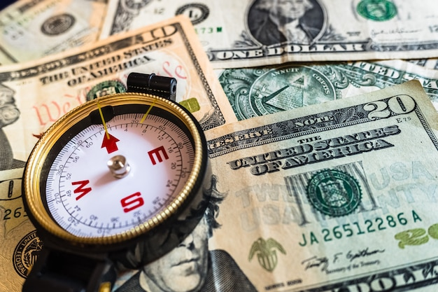 Close-up of a compass on dollar bills, guide for making smart investment decisions.