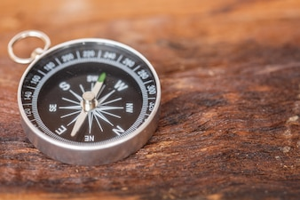 Close up compass on wood background