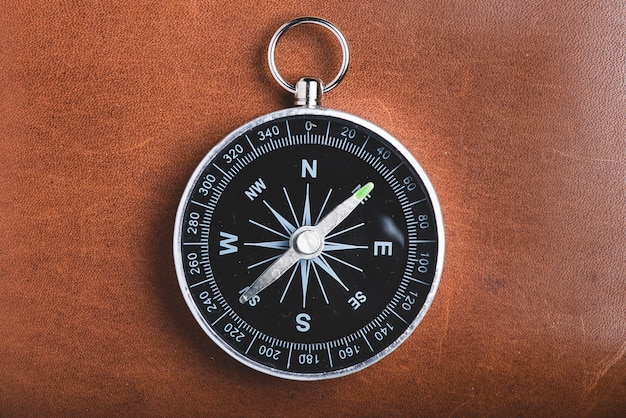 Close-up of compass on wooden background
