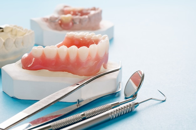Close up , complete denture or full denture on blue.