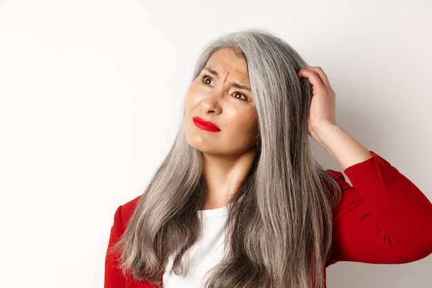 Close up of complicated asian mature woman scratching head, looking confused at upper left corner, standing and thinking over white wall.