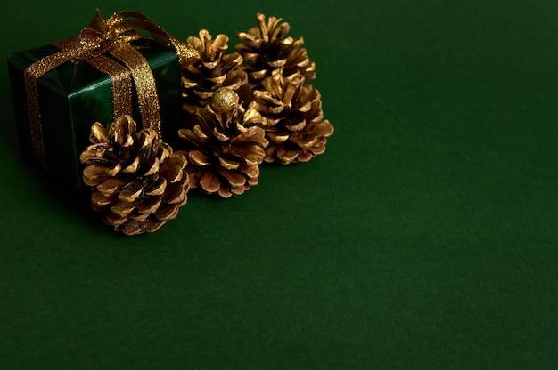 Макро композиция для новогодней и рождественской рекламы золотых сосновых шишек и небольшого роскошного подарка в блестящей зеленой оберточной подарочной бумаге с золотым бантом в углу зеленого фона с копией пространства