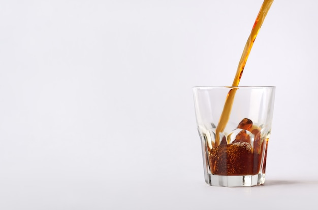The close-up composition with the dynamic flow of hot coffee  beverage is poured on the glass cup.image isolated on the white background.