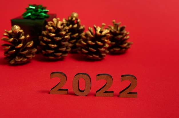 Close-up composition with wooden numbers, 2022 year on red colored background with blurred christmas gift box in shiny green wrapping gift paper and golden pine cones. copy space for advertising