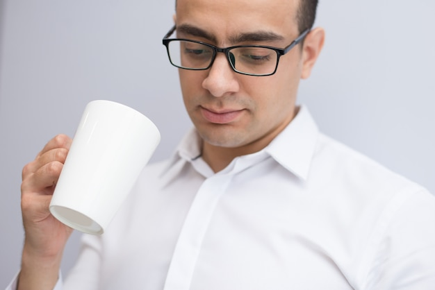 Close-up of concentrated businessman in glasses drinking coffee