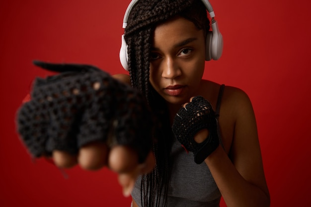 Close-up of concentrated young african athletic woman boxer in headphones and red boxing gloves striking a straight punch. contact martial art concept isolated on colored background with copy space