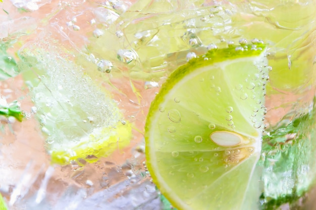 Close up concept on piece of lemon or lime in lemonade or mojito for wallpaper