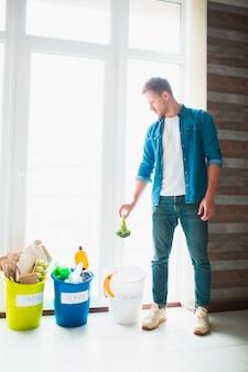 Концепция крупным планом. разберите мусор дома. есть три ведра для разных видов мусора. парень сортирует мусор на кухне.