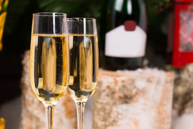Закройте концептуальные бокалы шампанского на элегантных бокалах флейты с бутылкой вина на заднем плане.