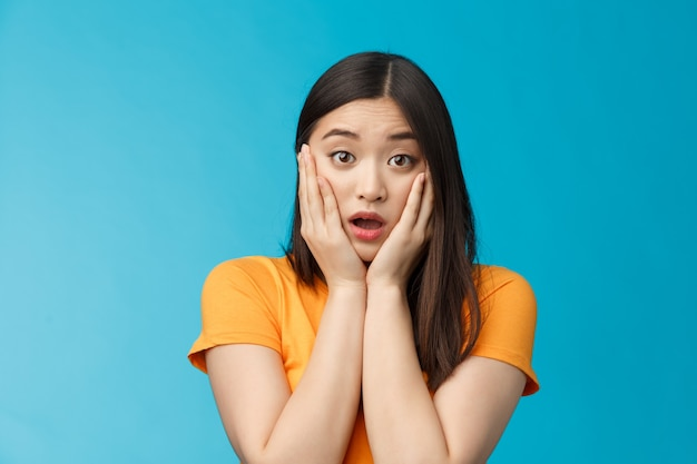 Close-up concerned shocked young timid asian girl gasping, dropping jaw feel sorry, pitty for friend open mouth stunned stare camera, grab face shook, speechless, frustrated, stand blue background.