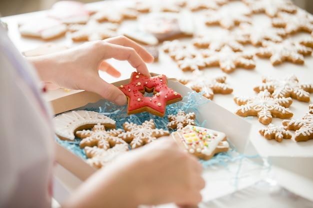 Primo piano del confettero mano imballaggio biscotti di pan di zenzero in b