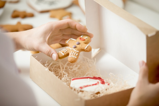 Close up of confectioner hand packing gingerman into a box