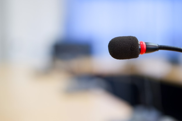 Close-up conference microphones in a meeting room is blurred in the  background.