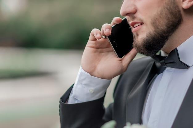 閉じる。携帯電話で話している自信のあるビジネスマン