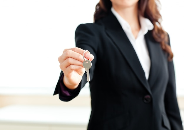 Close-up of a confident businesswoman holding a key