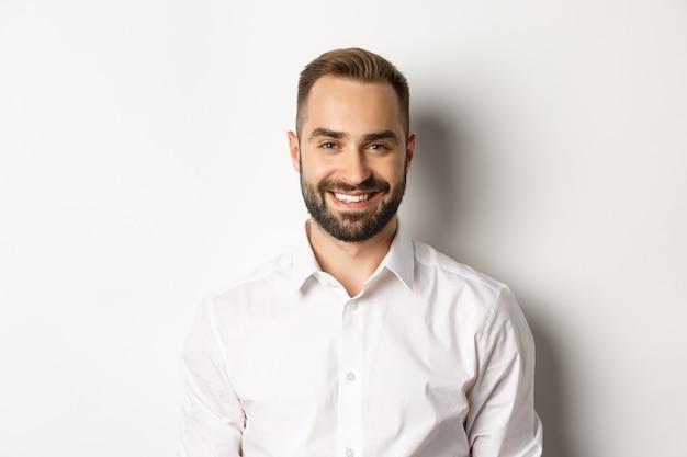 Primo piano del dipendente maschio fiducioso in camicia di colletto bianco che sorride alla macchina fotografica, in piedi sicuro di sé sullo sfondo dello studio.