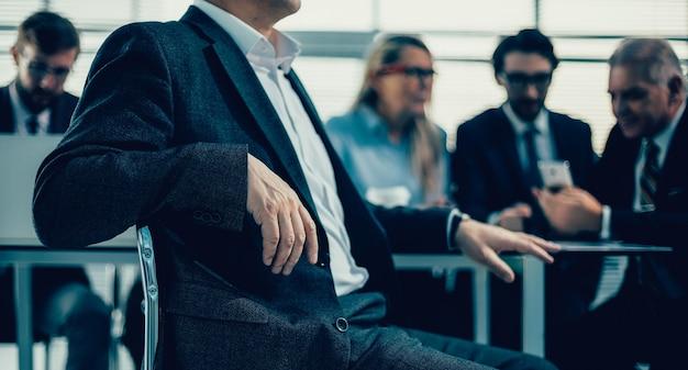 閉じる。机の前に座っている自信のあるマネージャー。ビジネスコンセプト