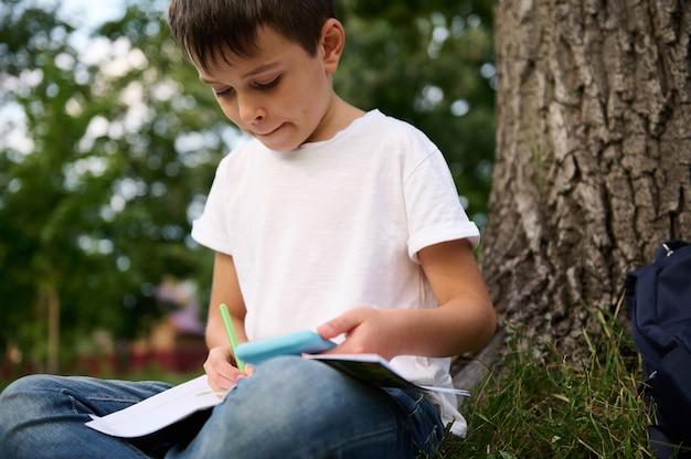 Крупный план. уверенный портрет умного ученика начальной школы, красивого умного школьника, делающего домашнее задание, отдыхающего в общественном парке, наслаждающегося отдыхом между уроками после первого дня в школе
