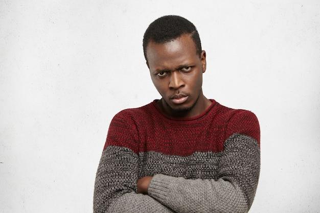 腕を組んで狂った不機嫌な表情で見つめている自信の若いアフロアメリカンの男性をクローズアップ