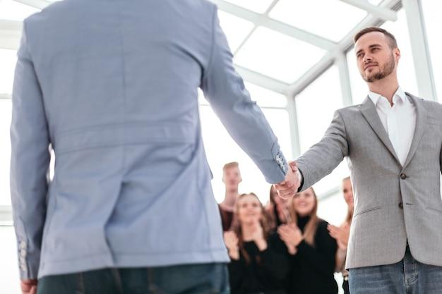 Закройте вверх. уверенные в себе молодые деловые люди встречают друг друга рукопожатием.