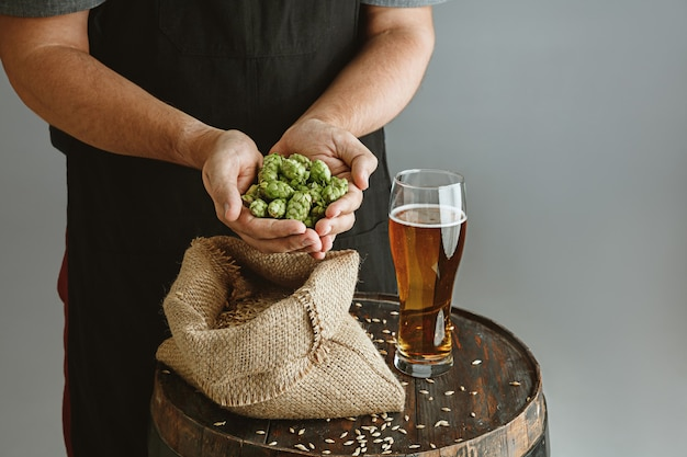 Close up of confident young man brewer with self crafted beer in glass on wooden barrel on grey wall.