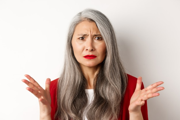 Close up of confused asian female manager with grey hair, wearing red blazer and makeup, spread hands sideways and staring puzzled at camera, white background.