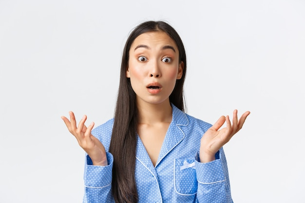 Primo piano di una ragazza asiatica confusa e scioccata in pigiama blu con sguardo sorpreso e alzando le mani, alzando le spalle, non riesco a capire cosa è successo, in piedi inconsapevole sfondo bianco.