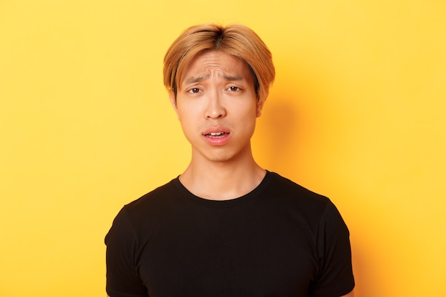 Close-up of confused and upset asian blond guy looking puzzled, open mouth and frowning perplexed, standing over yellow wall.