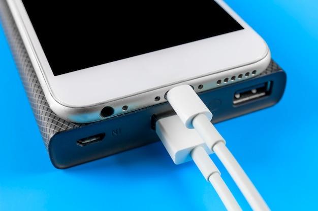 복사 공간 파란색 배경에 전원 은행 충전 연결 스마트 폰을 닫습니다.